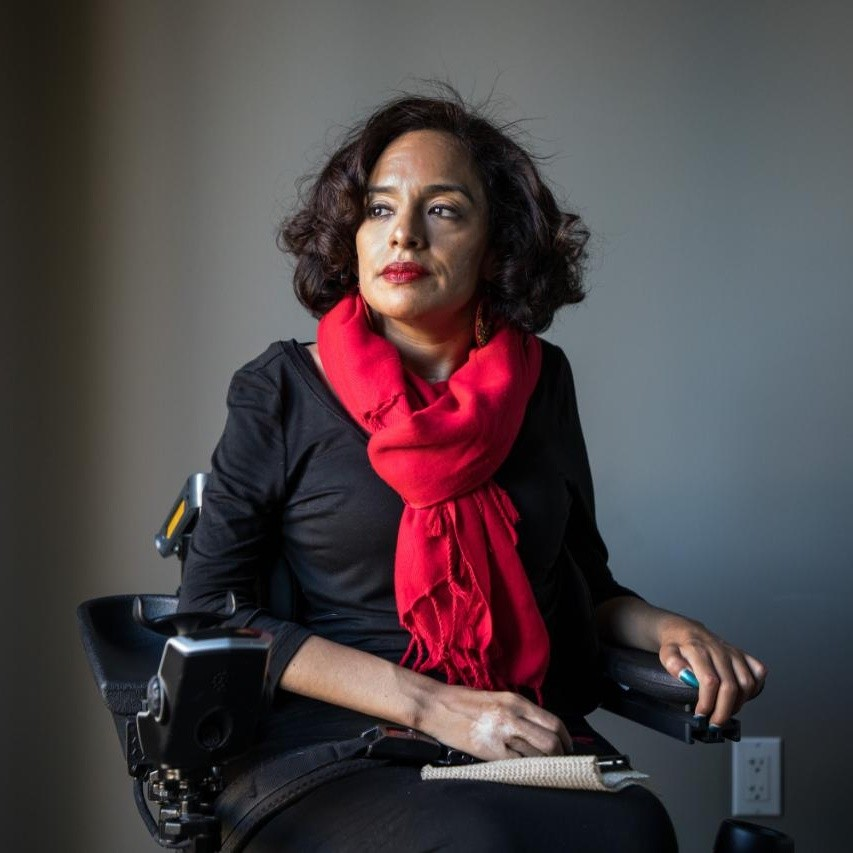 A latina woman with shoulder-length dark hair wearing a red scarf and a black shirt.  She sits in a power wheel chair and is looking off to the right away from the camera.