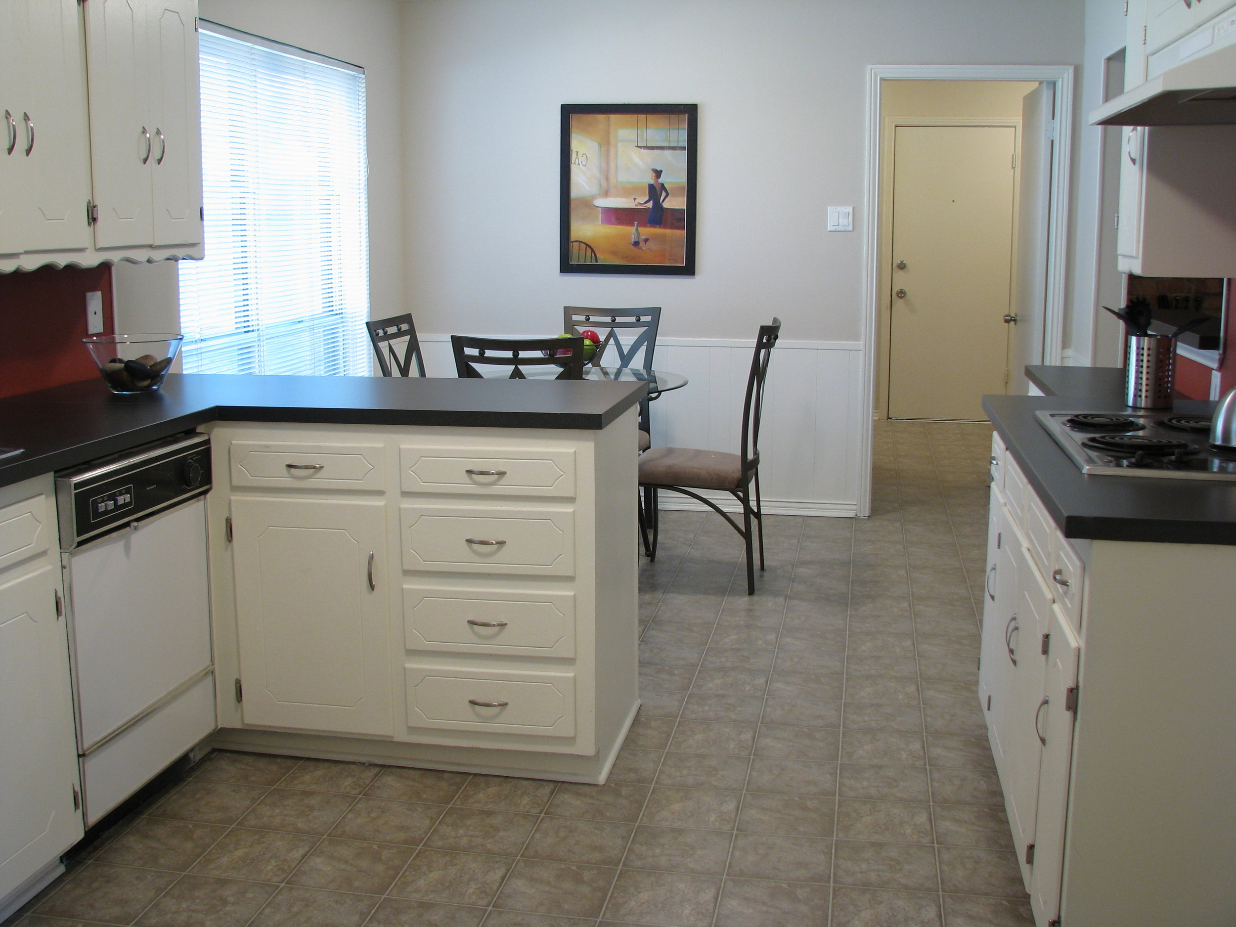 Kitchen after painting the cabinets, new linoleum, new laminant counter tops and staging