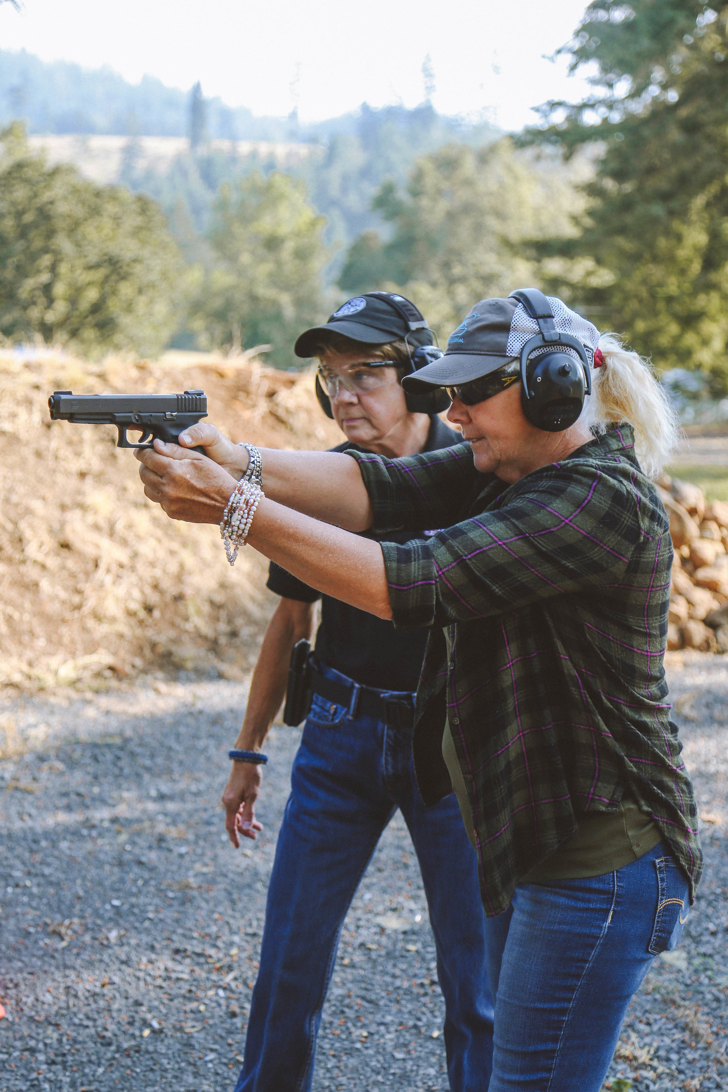 Carol helps student with proper form at the firearm range.