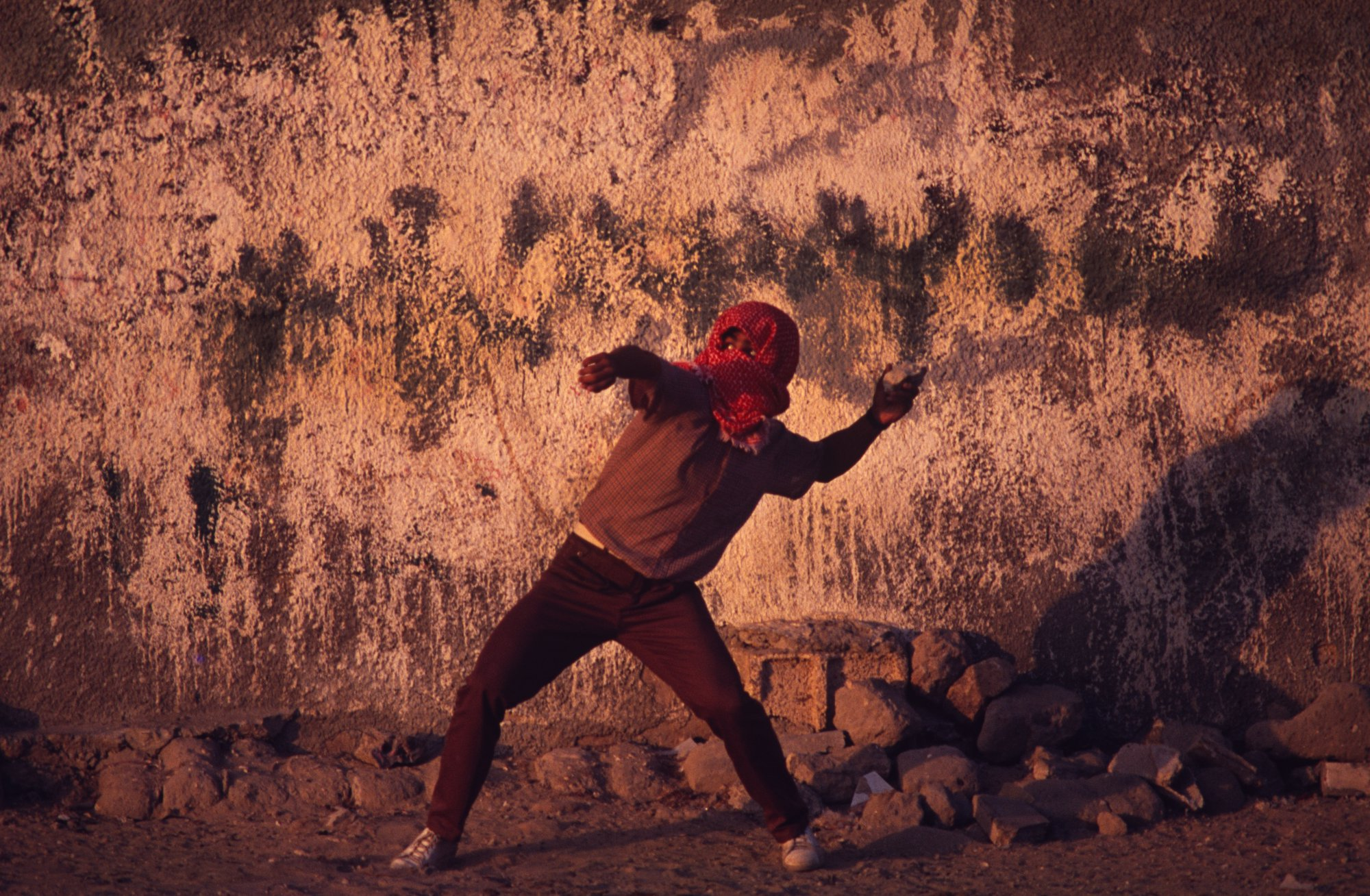 A member of the PLO hurls a rock (during the First Intifada) at Israeli Army soldiers in the Gaza Strip. 1992