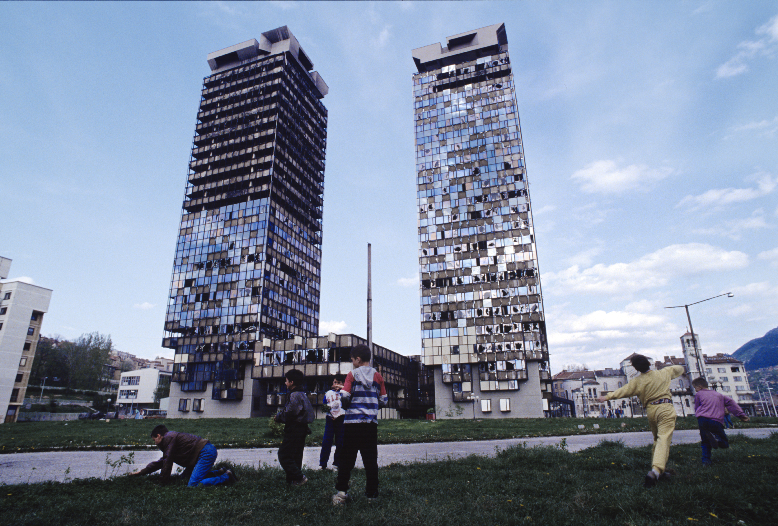 """A man collects flowers and wild grass to eat while children play in front of the """"Momo"""" and """"Uzeir"""" towers on Sniper Alley in downtown Sarajevo. 1995"""