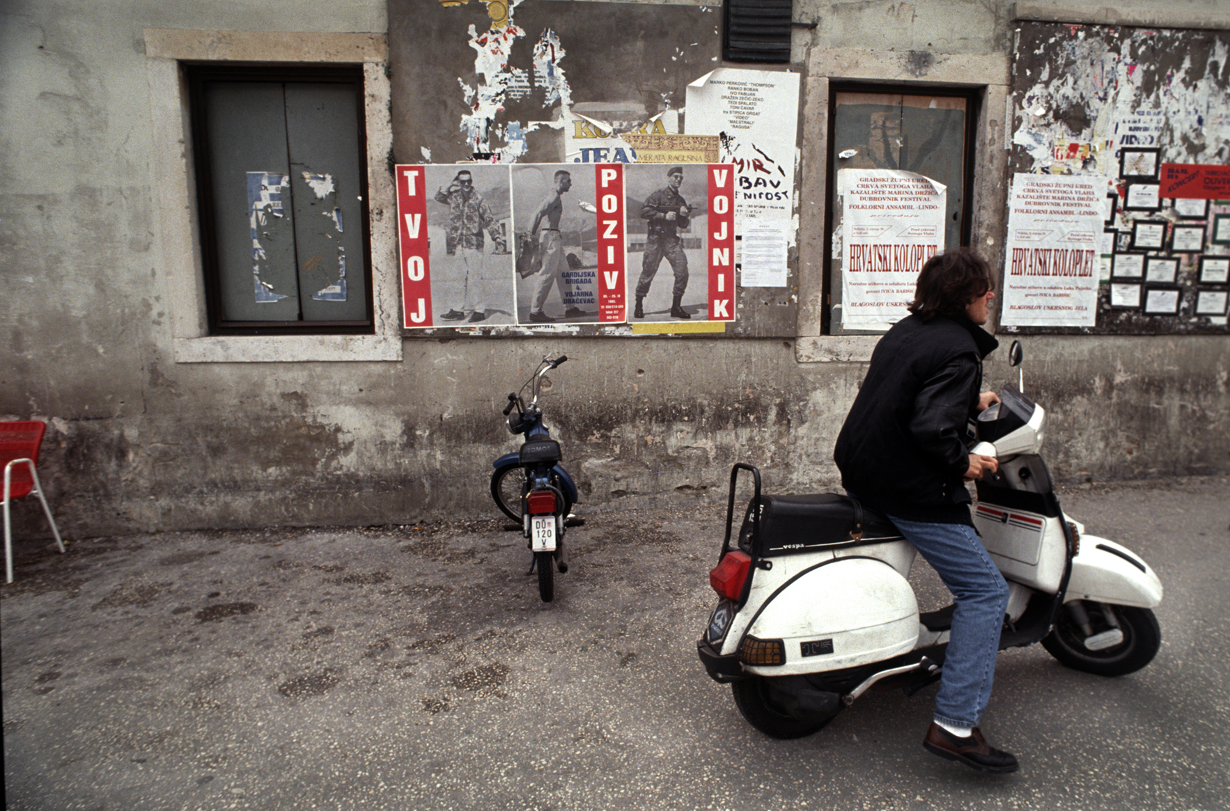 """""""Irony"""" The poster on the left shows a civilian to soldier transformation. The small white squares with black borders on the right are 'death notices' for soldiers killed during the war. Dubrovnik, Croatia. 1993"""