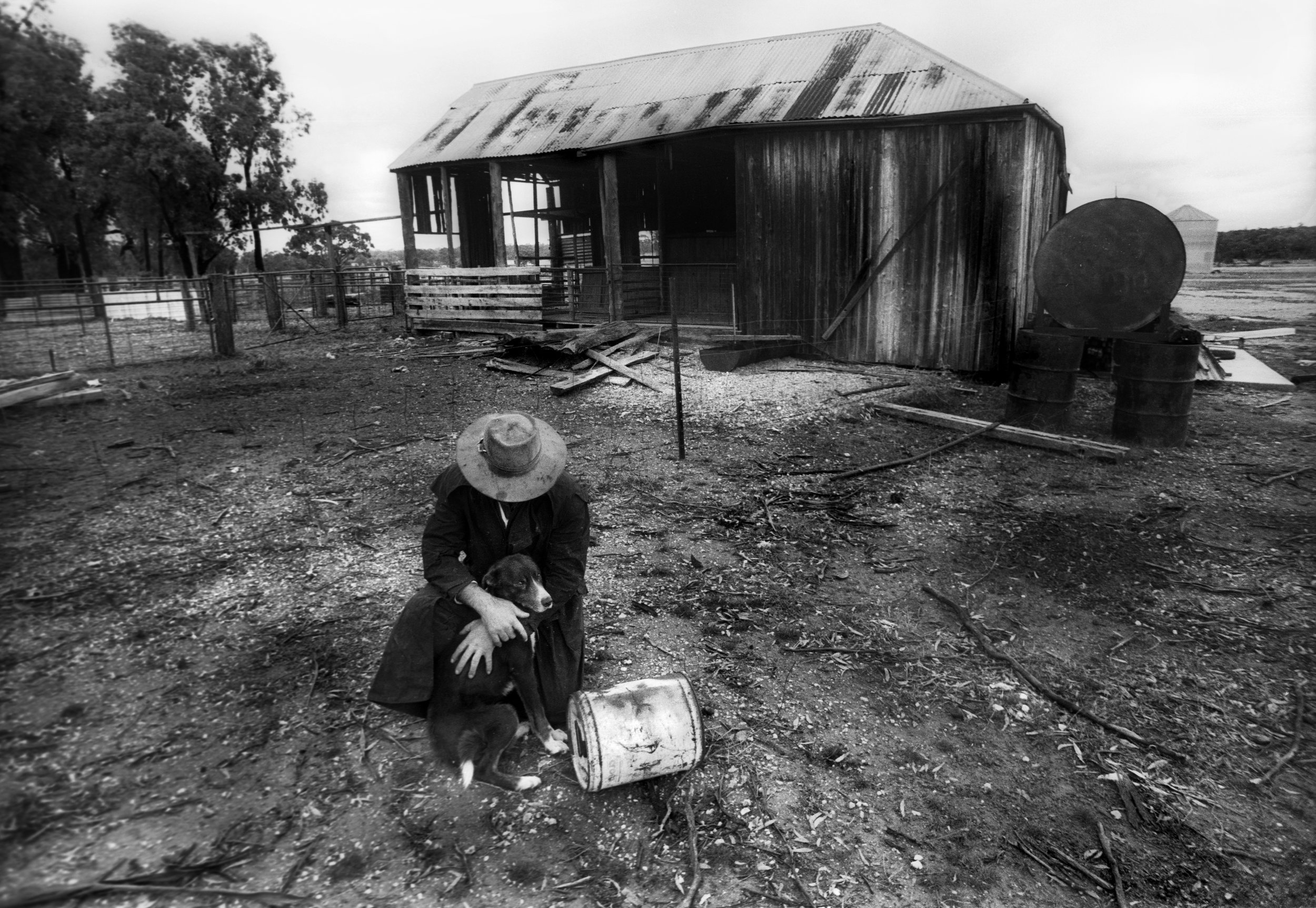 Drought stricken farmer and his dog on a sheep property near Bourke, outback NSW, Australia. 1997
