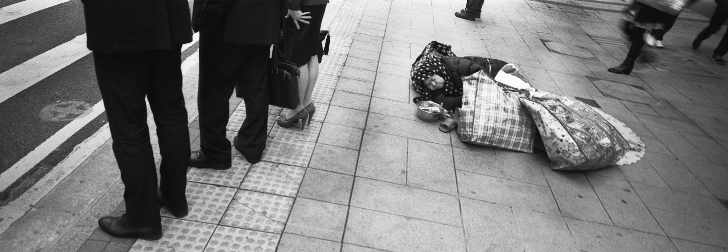 Business people and beggar. Hong Kong. 2014