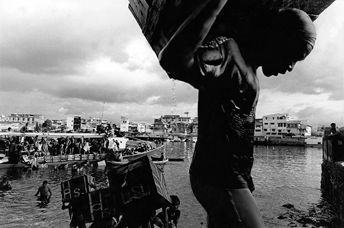 Unloading boats, Mandao Bay, Sulawesi. Bay and river system was polluted with mercury poisoning from illegal gold mining. 2002