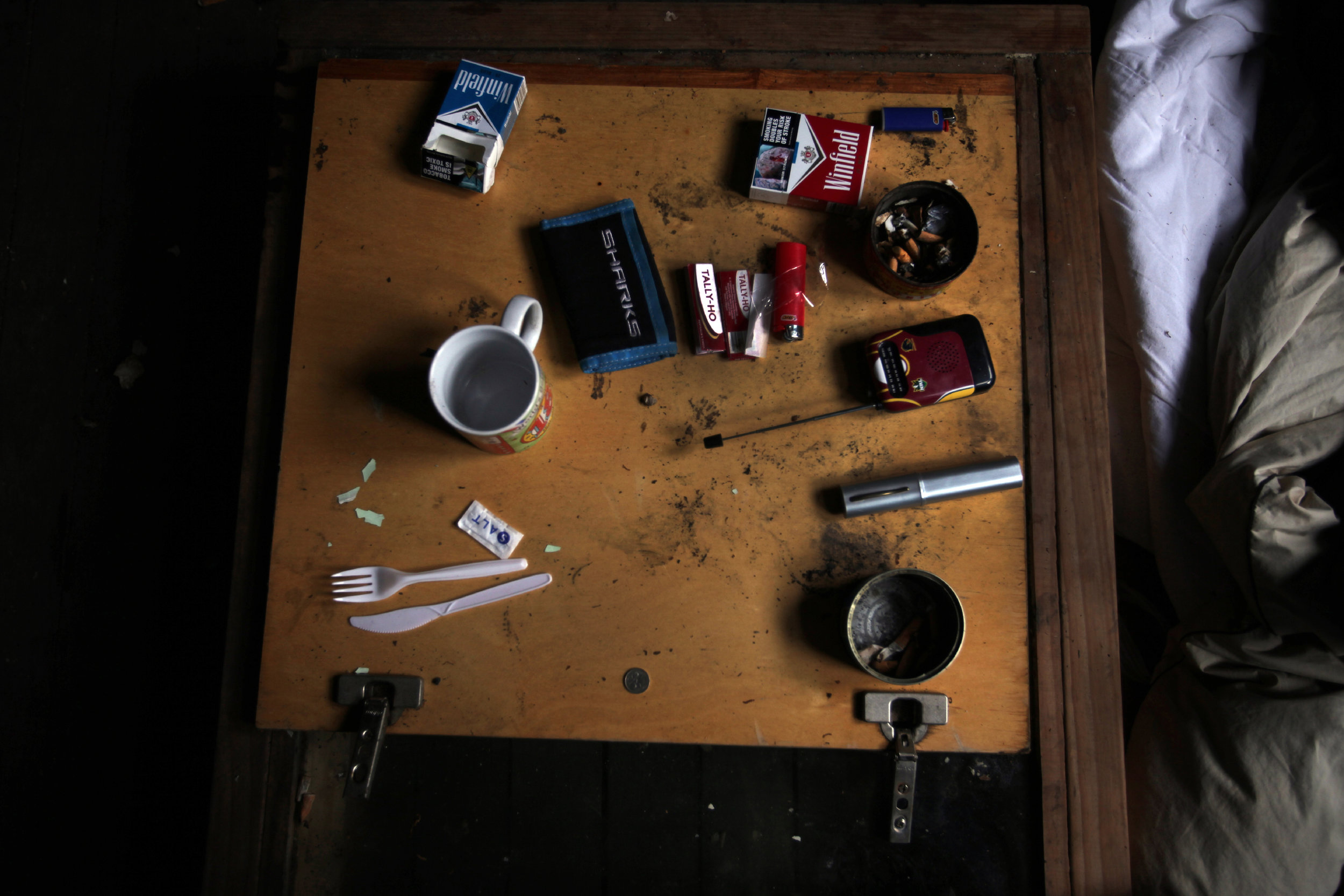 Denis's bedside table in the derelict building that is currently his abode.