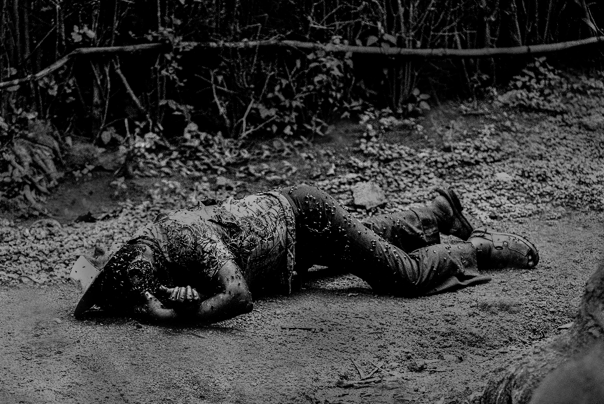 A Tutsi man felled in the front garden of his home. Many victims like this man appeared like still photographs - frozen in time -and peppered over the Rwandan landscape.