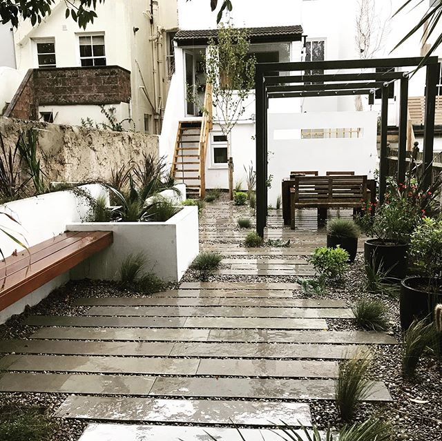 These pics were taken just as the last plant went in the ground and it started hammering down. I was hoping to get some sunny snaps but it hasn't stopped raining since! ☔️ This is a project we have just completed in central Brighton. New staircase, custom pergola with a feature wall, raised beds, floating bench and some lovely limestone plank paving and gravel supplied by Chandlers Building Supplies. The client came up with the design which we altered slightly to make it work. The boys worked hard on this one as access was very tight. 💪🏼And the planting scheme was created by the very talented Alick @fern_and_pine. Can't wait to go back next year and see how the plants are settling in. #landscapedesign #landscaper #landscaping #garden #gardendesignideas #brighton #brightonandhove #fiveways #prestonpark #homeimprovement