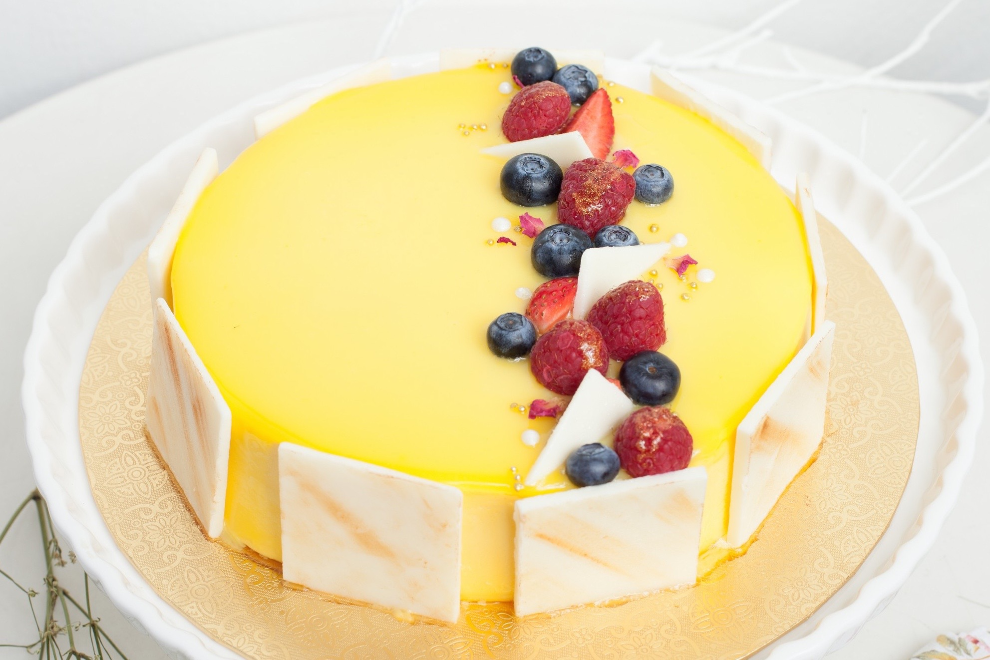 Mango Raspberry Entremet - Ø18 cm - Rp. 500.000,-Ø20 cm - Rp. 750.000,-Mango mousse with a center of raspberry jelly and almond dacquoise on top of a vanilla pâte sablée base. Garnished with fresh berries, dried rose petals and white chocolate decorations.