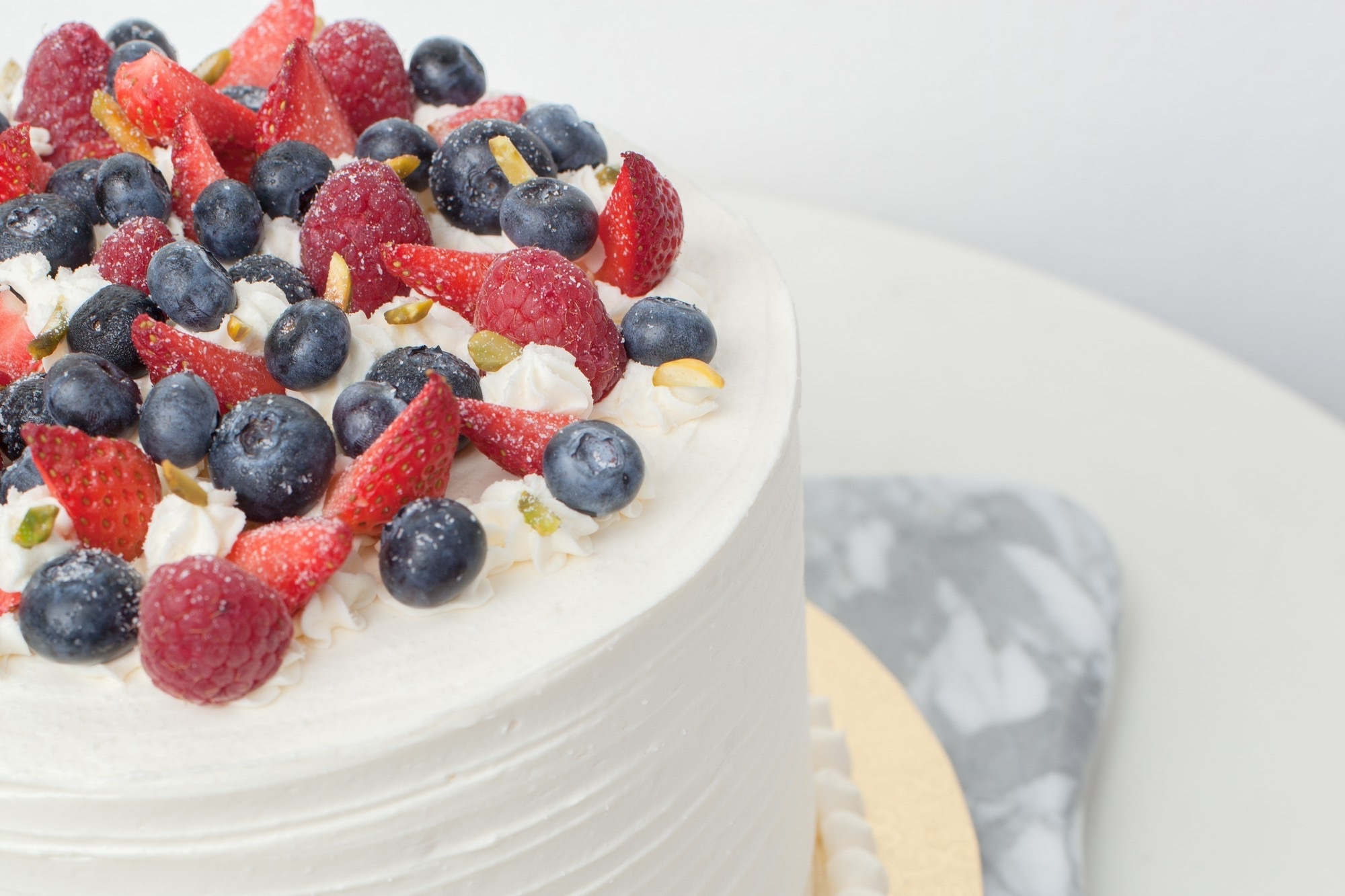 Triple Berry Cake - Ø18 cm - Rp. 800.000,-Ø22 cm - Rp. 1.200.000,-Ø26 cm - Rp. 1.500.000,-Four layers of vanilla genoise filled with crème chantilly,fresh raspberries, blueberries and strawberries. Topped with more berries and pistachio slices.