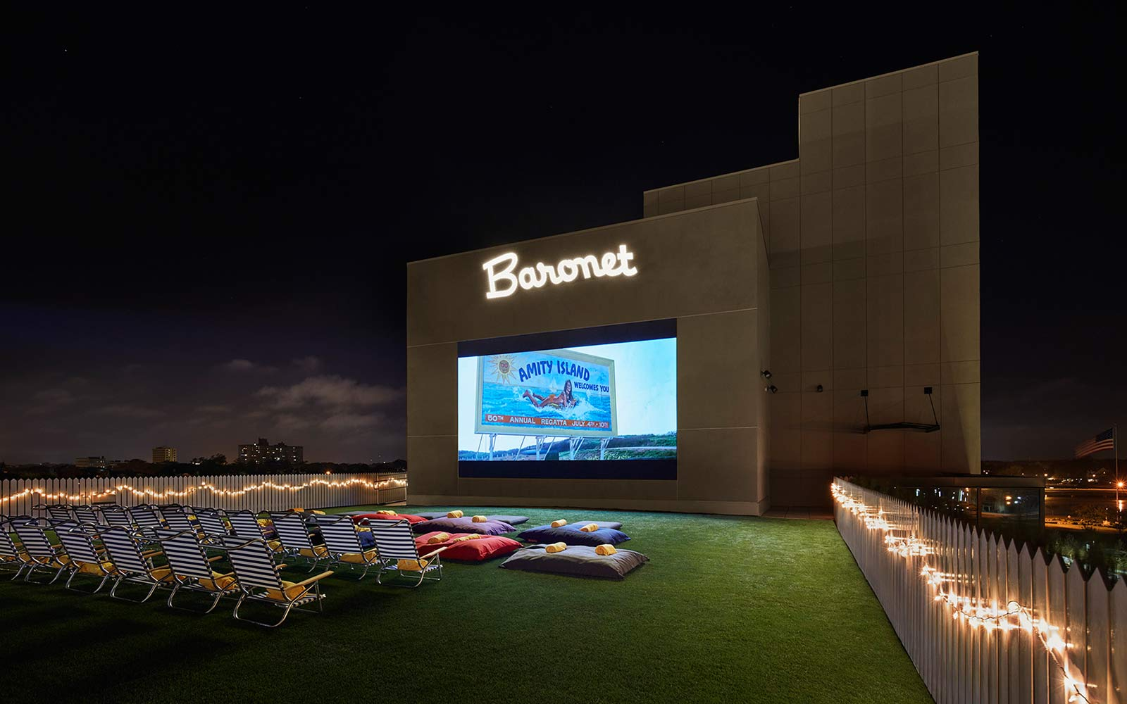 Movie screen under Baronet sign with seating in front.