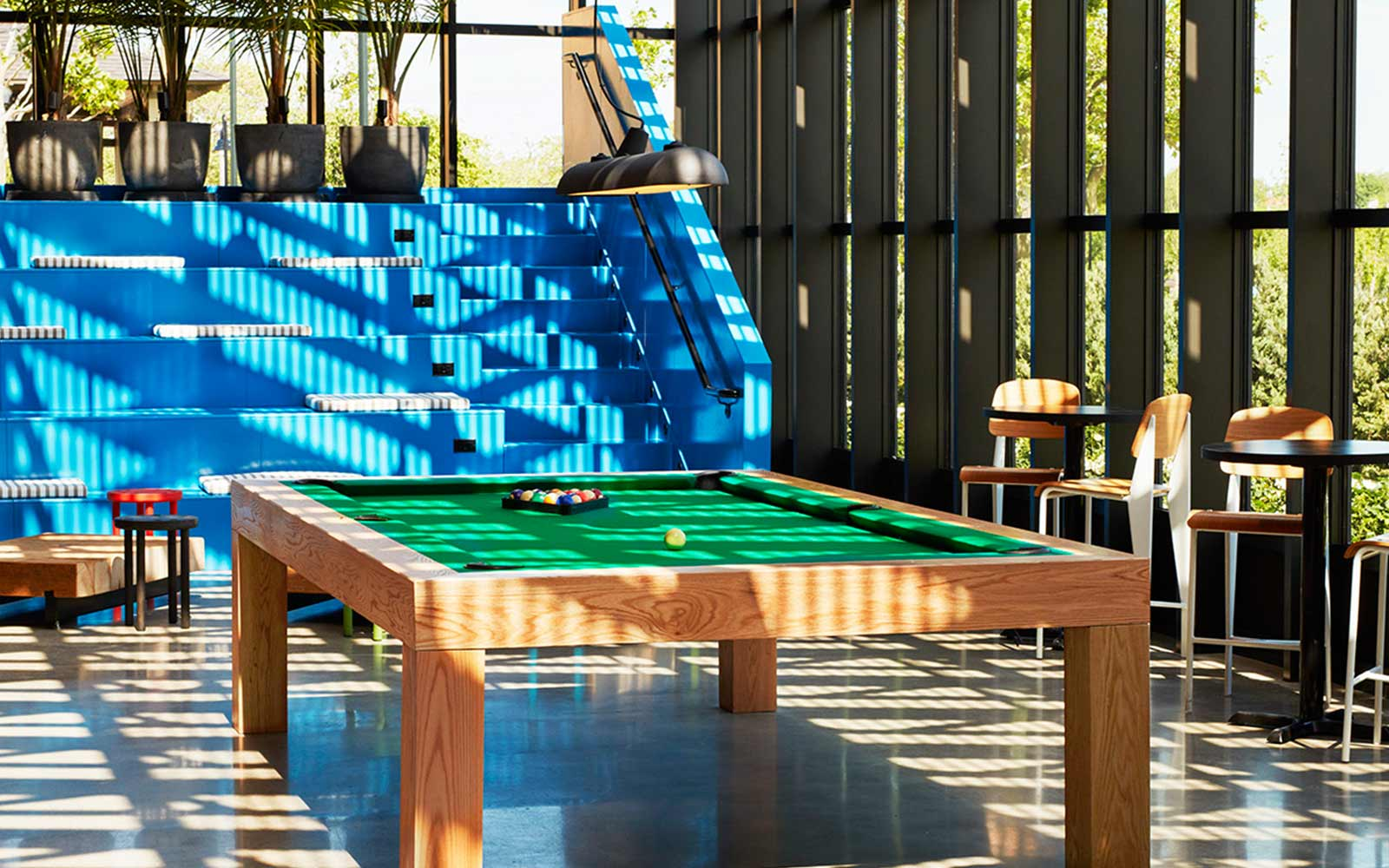 Pool table with blue bleacher seating in the background