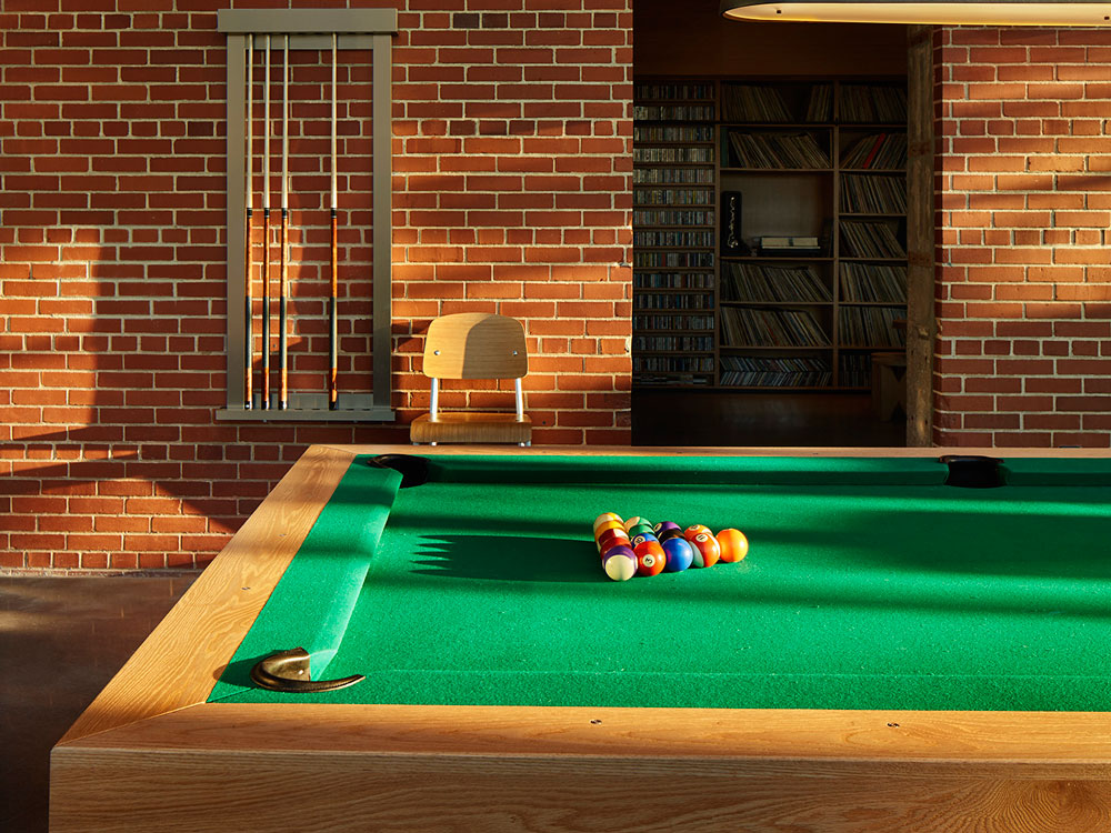 Pool table. Brick walls behinds.