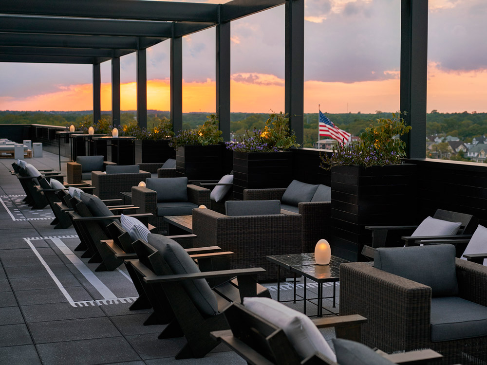 Rooftop bar. Empty chairs and couches. Sunset in background.