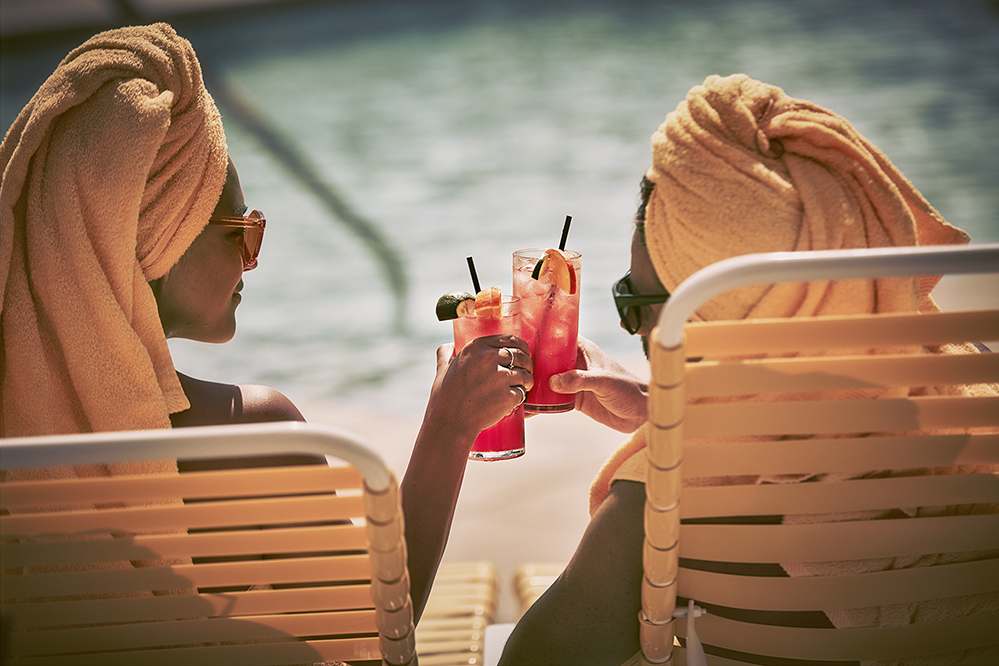 Two girls clinking red drinks. Yellow towels in their hair. On yellow beach chairs around the pool.