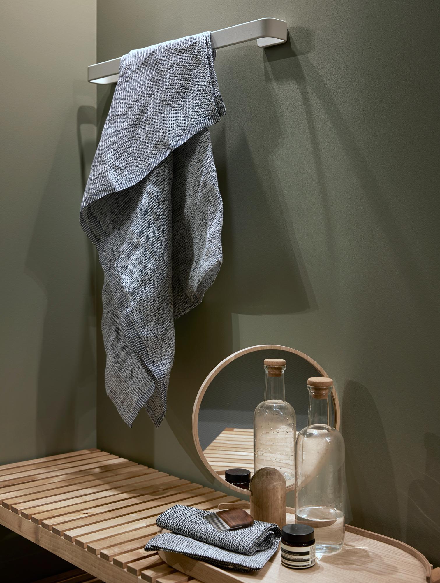 Molger benk i bjørk fra IKEA brukes til oppbevaring av håndkler itillegg som sittebenk.