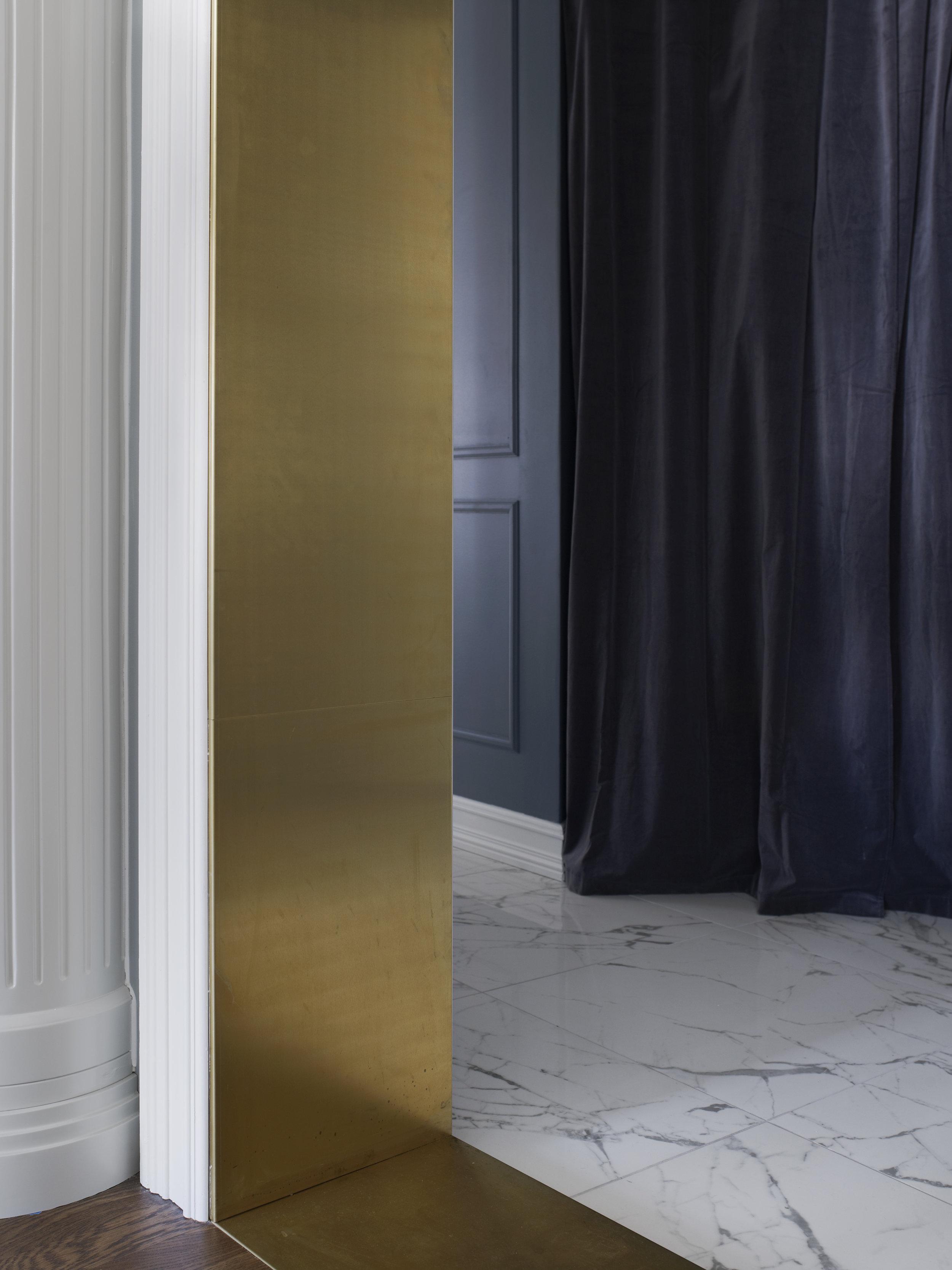 Eldre bygg har ofte skjeve gulv og overganger med høydeforskjell mellom rommene må tilpasses - som denne løsningen med dørramme i messing mellom entré og kjøkken.