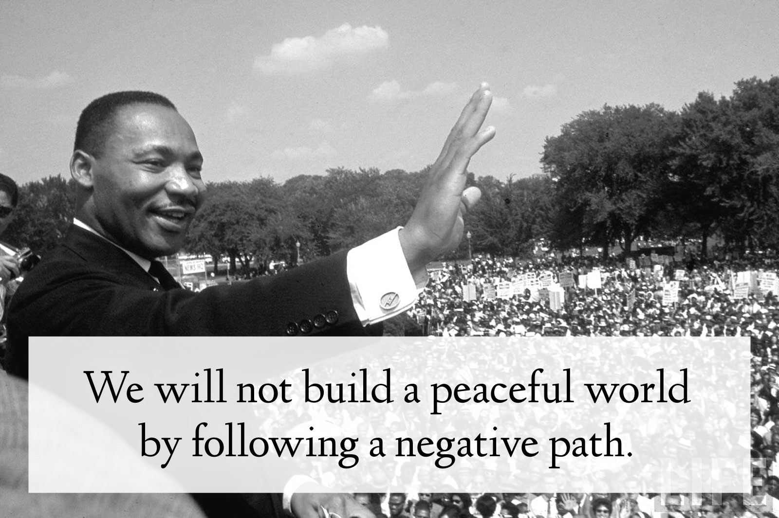"Image of Dr. King smiling and waving, in front of a huge crowd. The quote says ""We will not build a peaceful world by following a negative path."""