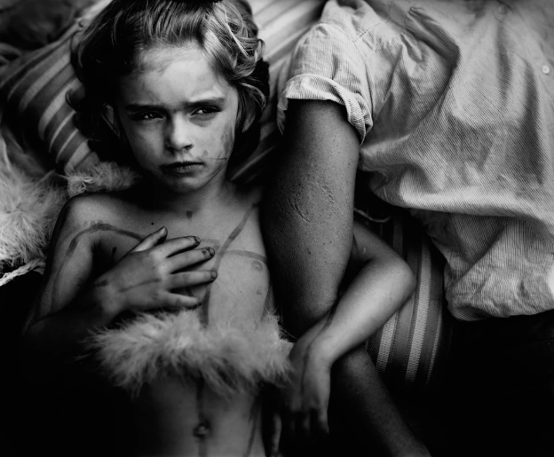 """Jessie Bites"" (1985) one of the many powerful moments captured by Sally Mann of her family. To be fair, however, Mann's photos are not true ""small moments"" but fictional accounts of small moments; she works in large format and prepares her shots carefully. For me, still, they inspired a lot of small-moment photography."