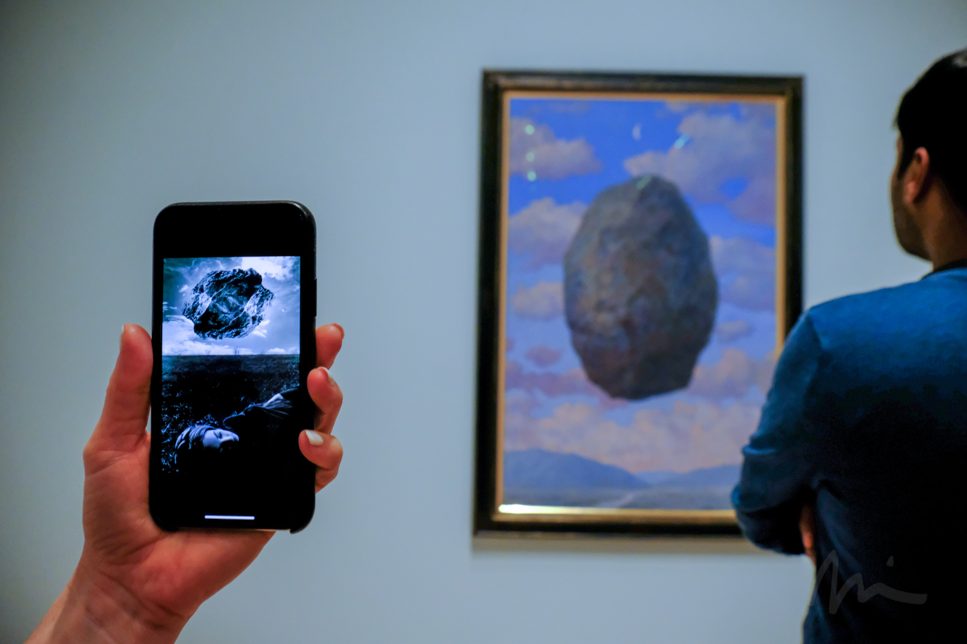 "Uelsmann's ""Magritte's Touchstone"" (1965) on a phone next to one of Magritte's floating stones at SFMOMA."
