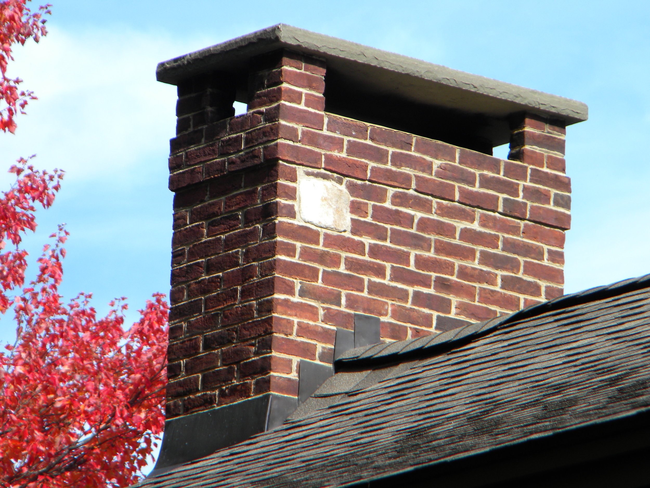 This is a close-up of the chimney shown above. Note the corbeling, counterflashing on the sidewall (integrated with step flashing beneath the shingles), apron flashing in front, and stone rain cap. Photo by Jay Cox.