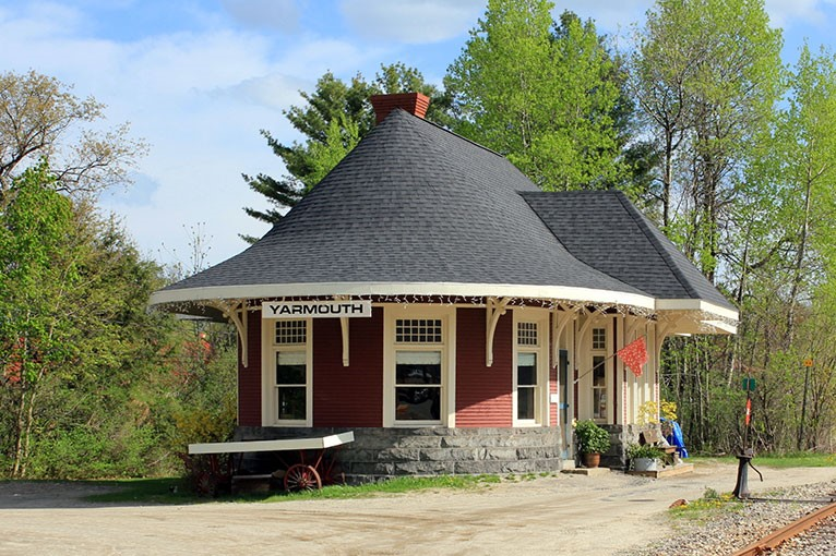 Grand Trunk Railroad Depot - The iconic 1906 depot is located on Main Street in the heart of Yarmouth Village and is a delightful reminder of our transportation heritage. The building retains many original station features including beautiful bead board walls, light fixtures, fireplace, and ticket window. It had been owned by the Yarmouth Village Improvement Society for more than 50 years and it had been leased as a florist shop since the early 1970s. After many years of faithful caretaking, the owner decided the time was right to sell the property to a new steward and worked with Maine Preservation to find a preservation-minded buyer.Ford Reiche, an enthusiastic support of historic property rehabilitation and adaptive reuse, purchased the deport for use as commercial office space. A branch of Gorham Savings Bank will open in the depot in 2019.