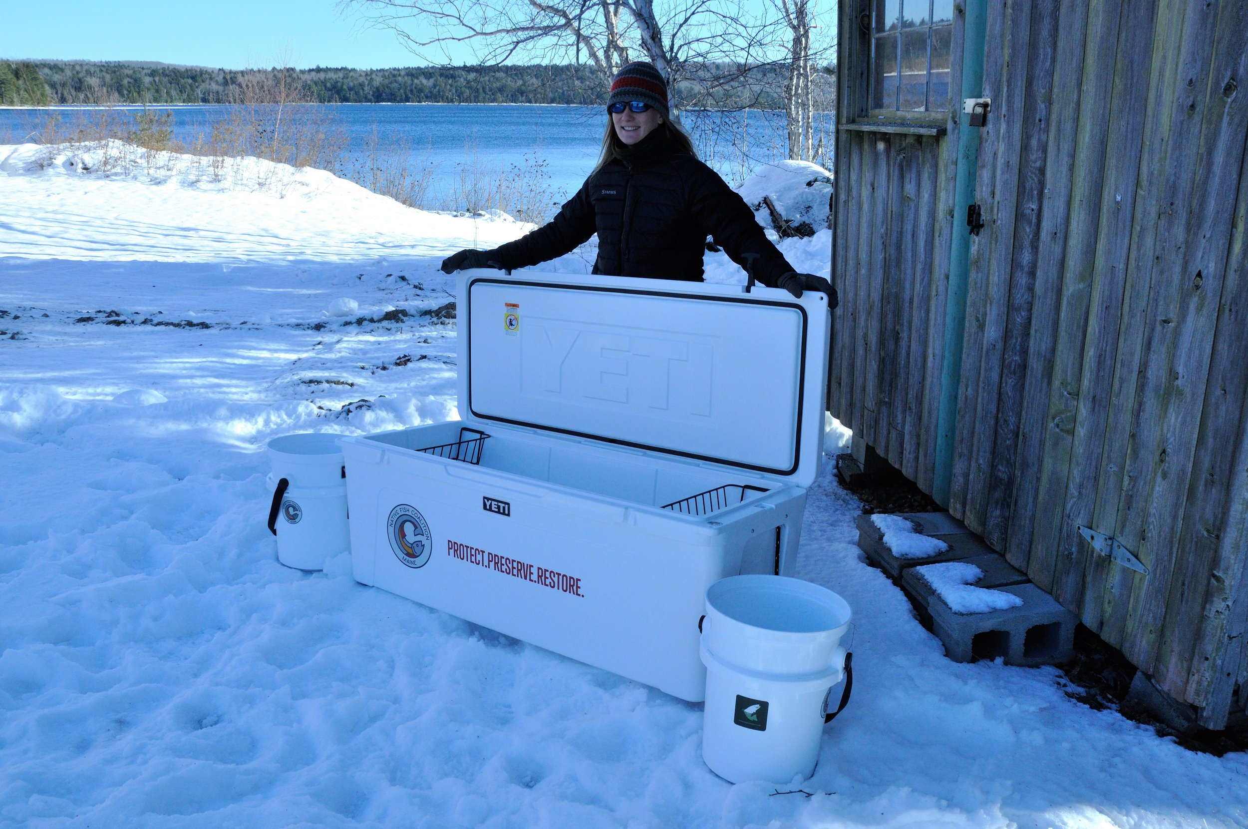 Maine NFC Chair Emily Bastian with cooler and buckets donated to UMaine for the ongoing Floods Pond Arctic Charr Study.