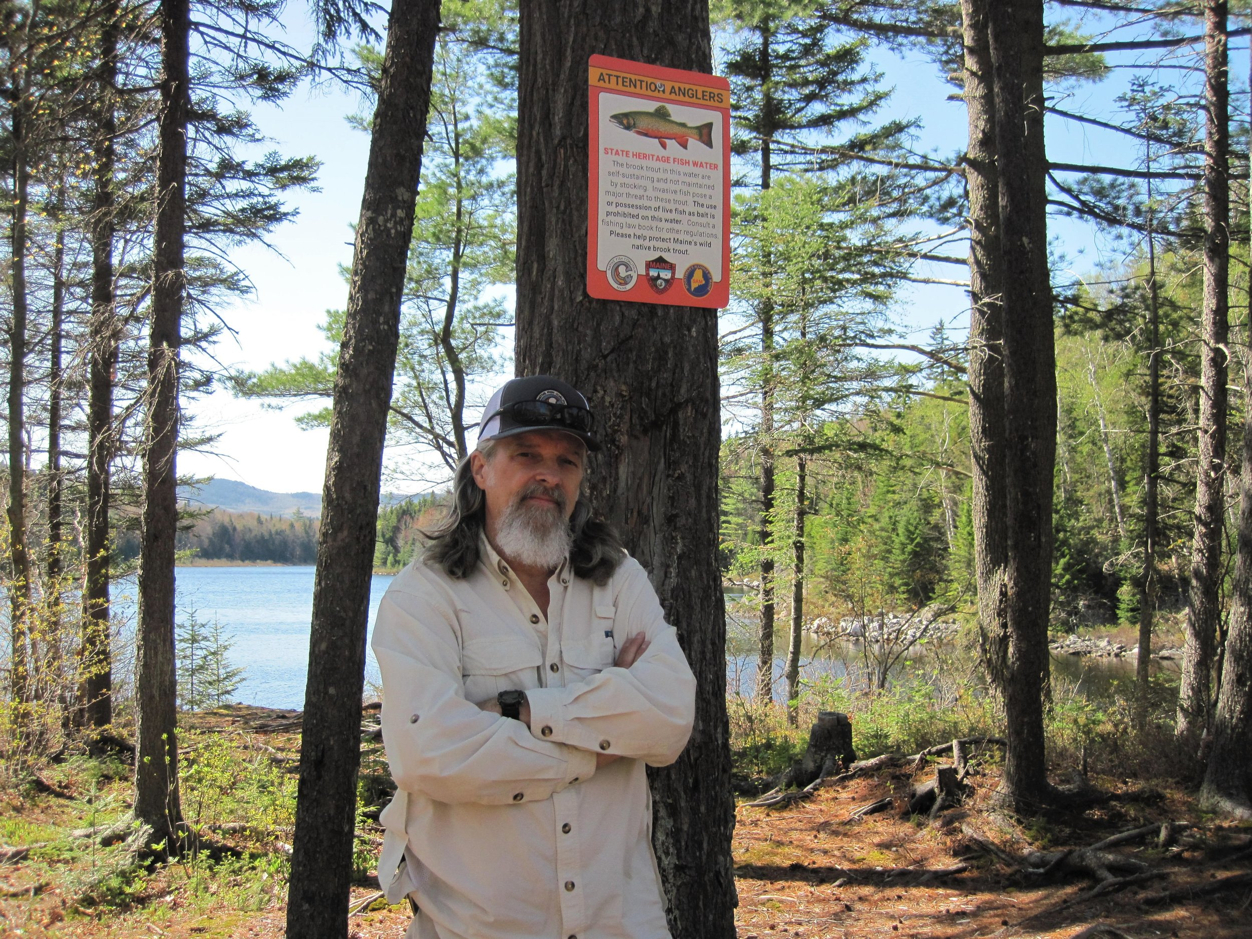 NFC National Vice Chair and Maine board member, and early proponent of Maine's State Heritage Fish law, Bob Mallard standing under the first State Heritage Fish sign posted as part of an initiative undertaken by Maine NFC in 2018, thirteen years after first presenting the idea to the powers that be.