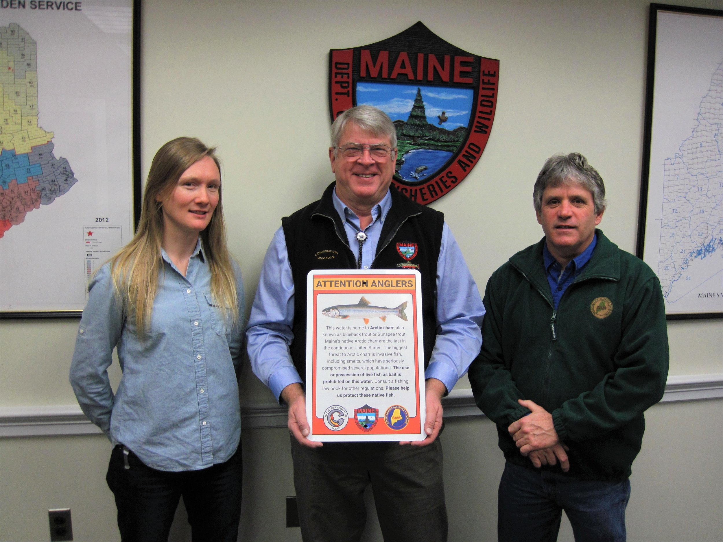 Maine NFC Chair Emily Bastian, former MDIFW Commissioner Chandler Woodcock, and SAM Executive Director David Trahan with the draft Arctic charr sign.