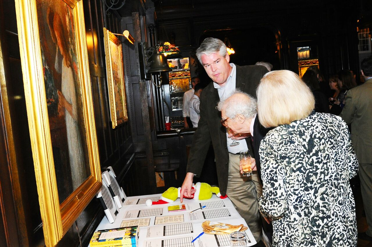 Sheldon & Margery Harnick & guest perusing Auction items.jpg