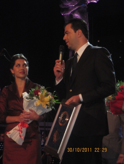 Encompass First Place Winner Sara Heaton onstage with the Mayor of Tirana, Albania, who is presenting her with her award