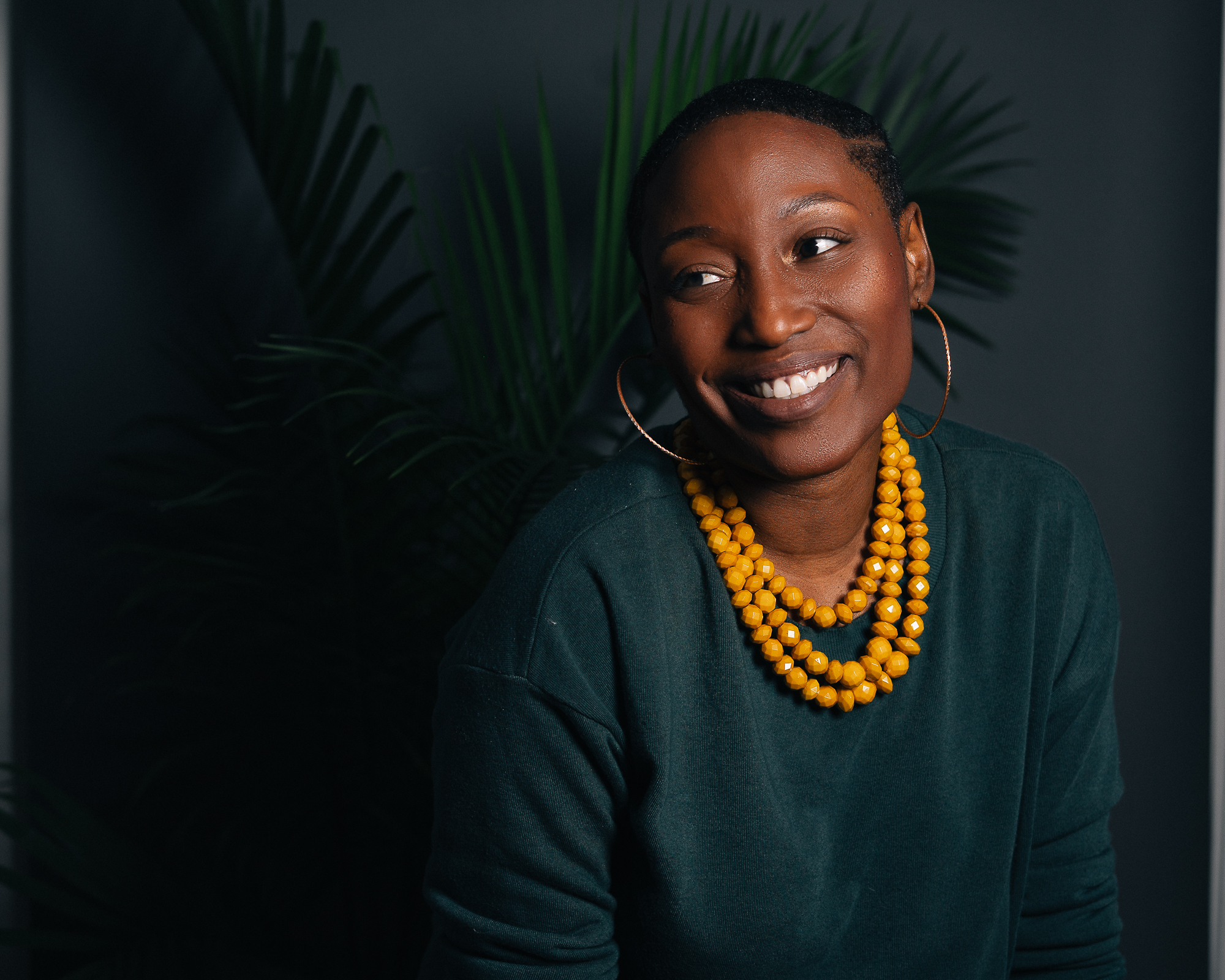toni black dallas photographer in green sweater with yellow necklace