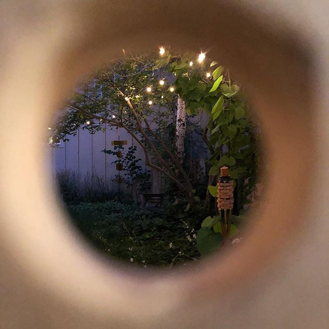 Prepping for @fireflyhandmade tomorrow and caught this twinkly garden view through a peg hole in the @jaspersocialclub display. 👁 🕳