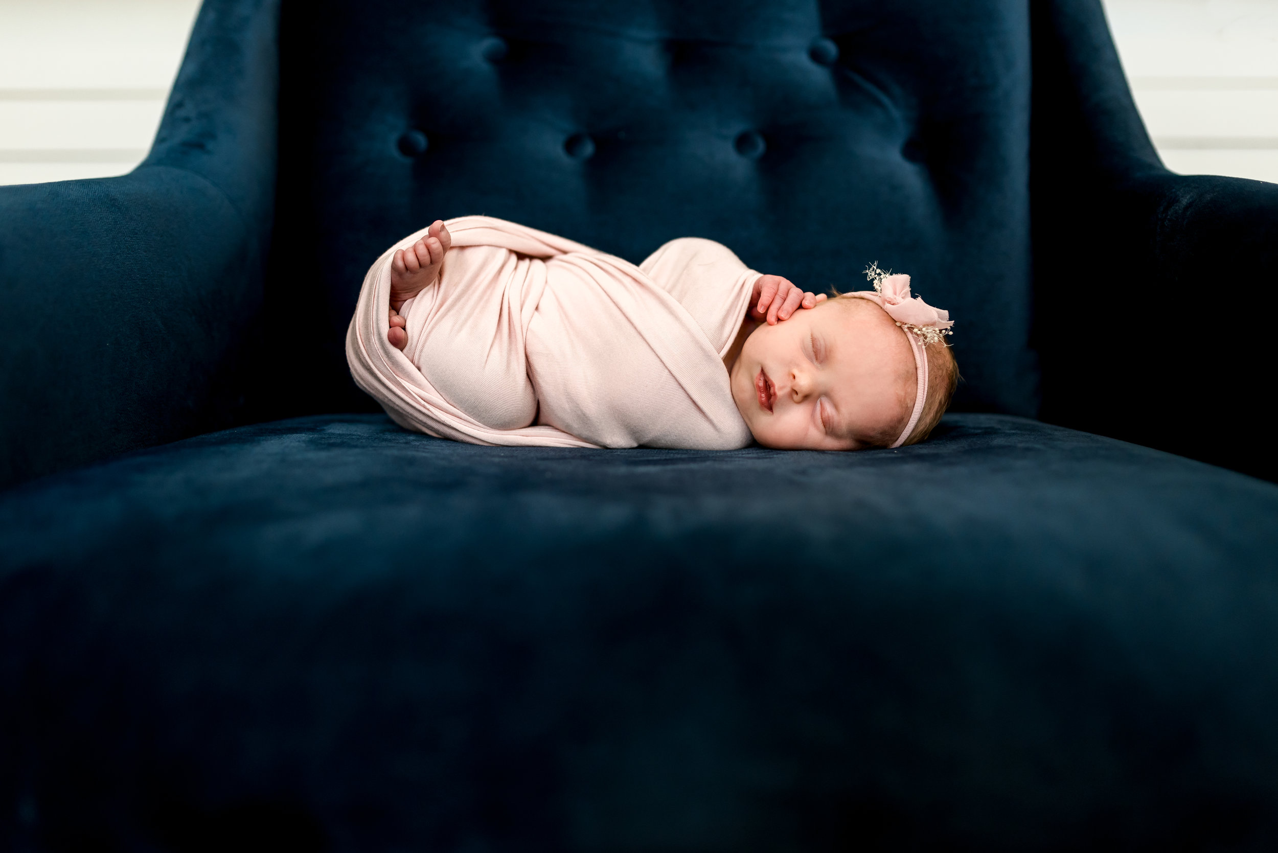 Sweet baby girl swaddled in pink, posed on a beautifully modern chair in this Houston, TX home.