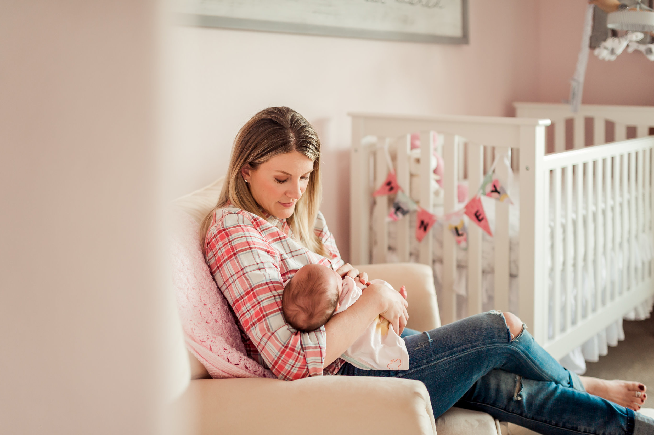 Newborn photographer, Dear Marlowe Photography, captures a mother rocking her baby girl in a beautiful pink and white nursery.