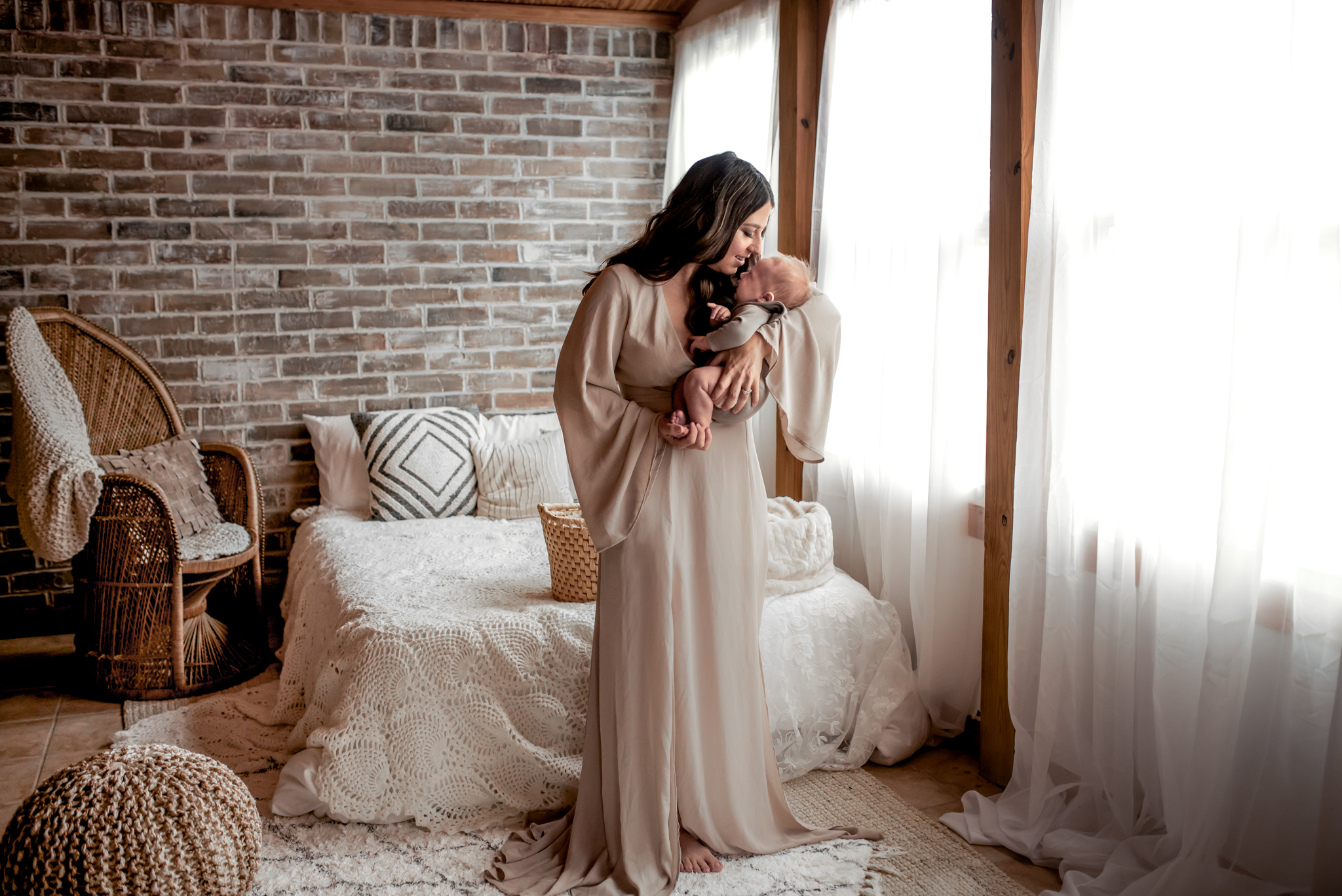 Beautiful mom and her baby boy in a Houston, TX natural light, boho studio with a brick wall, textures accents, peacock chair, and neutral details.