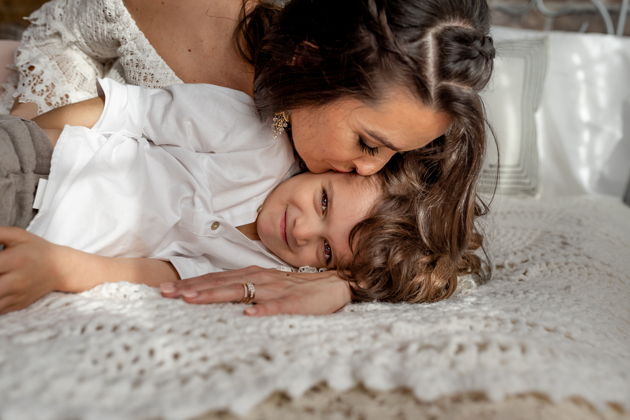 Beautiful mom and her baby boy in a natural light, boho studio with a brick wall, textures accents, peacock chair, and neutral details. Kisses and smiles all around!
