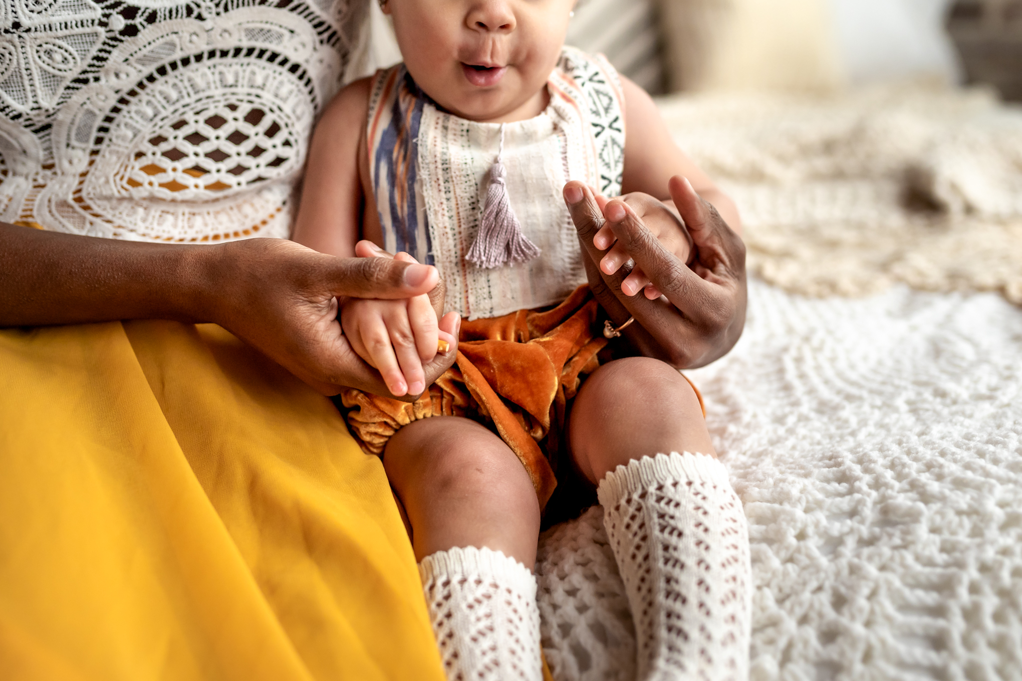 Beautiful Mommy and Me session with mom and her baby girl in a Houston, TX natural light, boho studio with a brick wall, textures accents, peacock chair, and neutral details. Sweet smiles and holding hands make for a sweet moment between mom and baby.