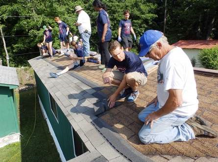 2016 Bike and Build group helping fix a roof alongside our construction crew.
