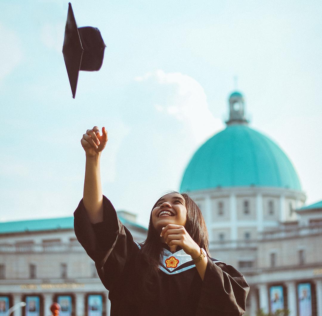 Happy graduate tossing cap.