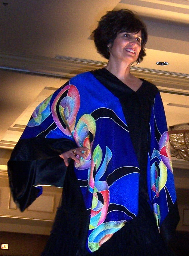 """SHELLS PONCHO""   Dyes on jacquard silk  ""Shells Poncho"" is being modeled at the Uncommon Threads Fashion Runway and Boutique Show of 2006. Models wearing my other four pieces were on the stage together, showing off my collection."
