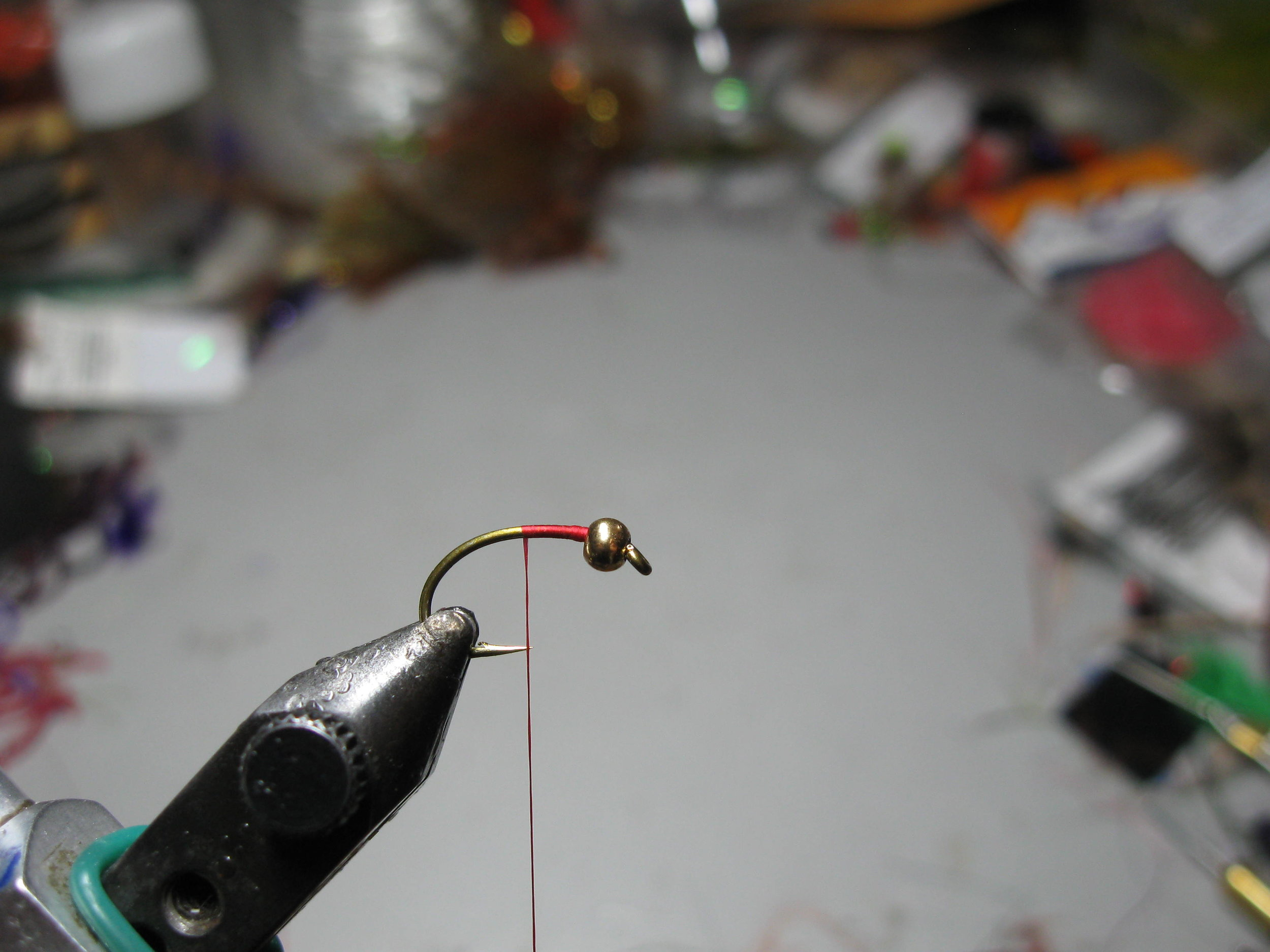 1.  Debarb hook and insert into vise . Thread the hook with a suitable bead and then wind a layer of touching thread turns along the shank.