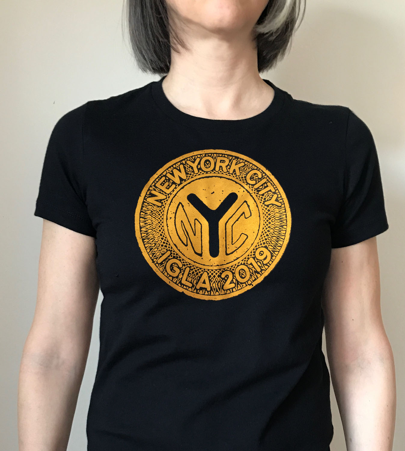 Women's black fitted t-shirt with vintage metallic gold token  $18