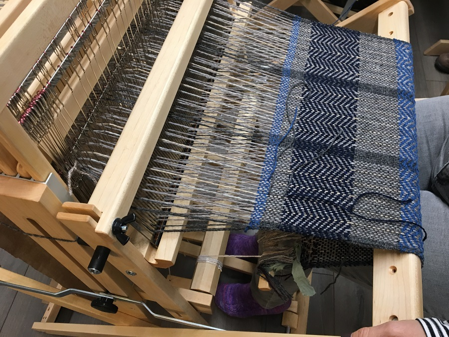 Such a professional looking piece! Surface threads get cut off at the end. Treadling in sock feet - love the purple socks!