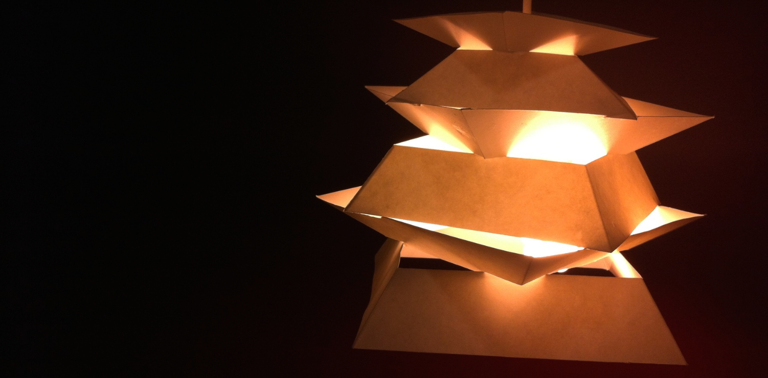 Derived from the simplistic structures of pagodas, Sutakku both reflects and traps light. Its various sized trapezoidal tiers only allow soft light to escape from the edges, as the rest gently glows from within.  From this model of the final design, you can see how the placement of these tiers prevent any harsh light from leaving and instead project the light from the bulb upwards against the fixture itself.
