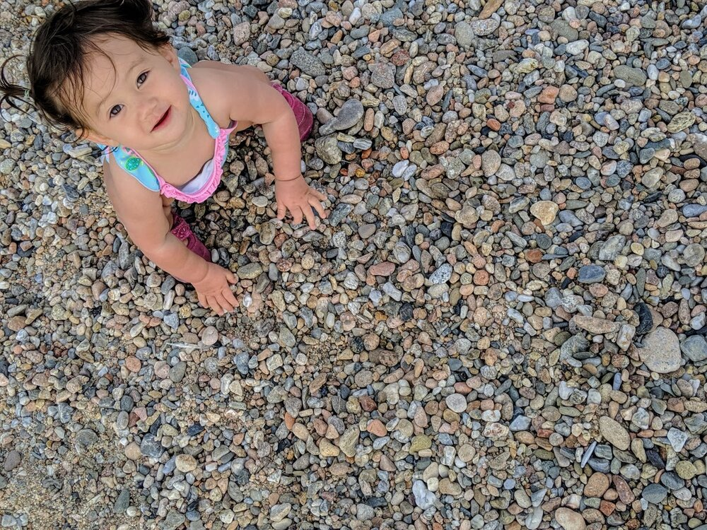 Petra was mesmerized by the pebbles on the beach.