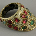 Northern India | Archer's thumb ring; gold set with rubies and emeralds, with white enamel lotus motifs. Green enamel lotus design on the inside.| 19th century |