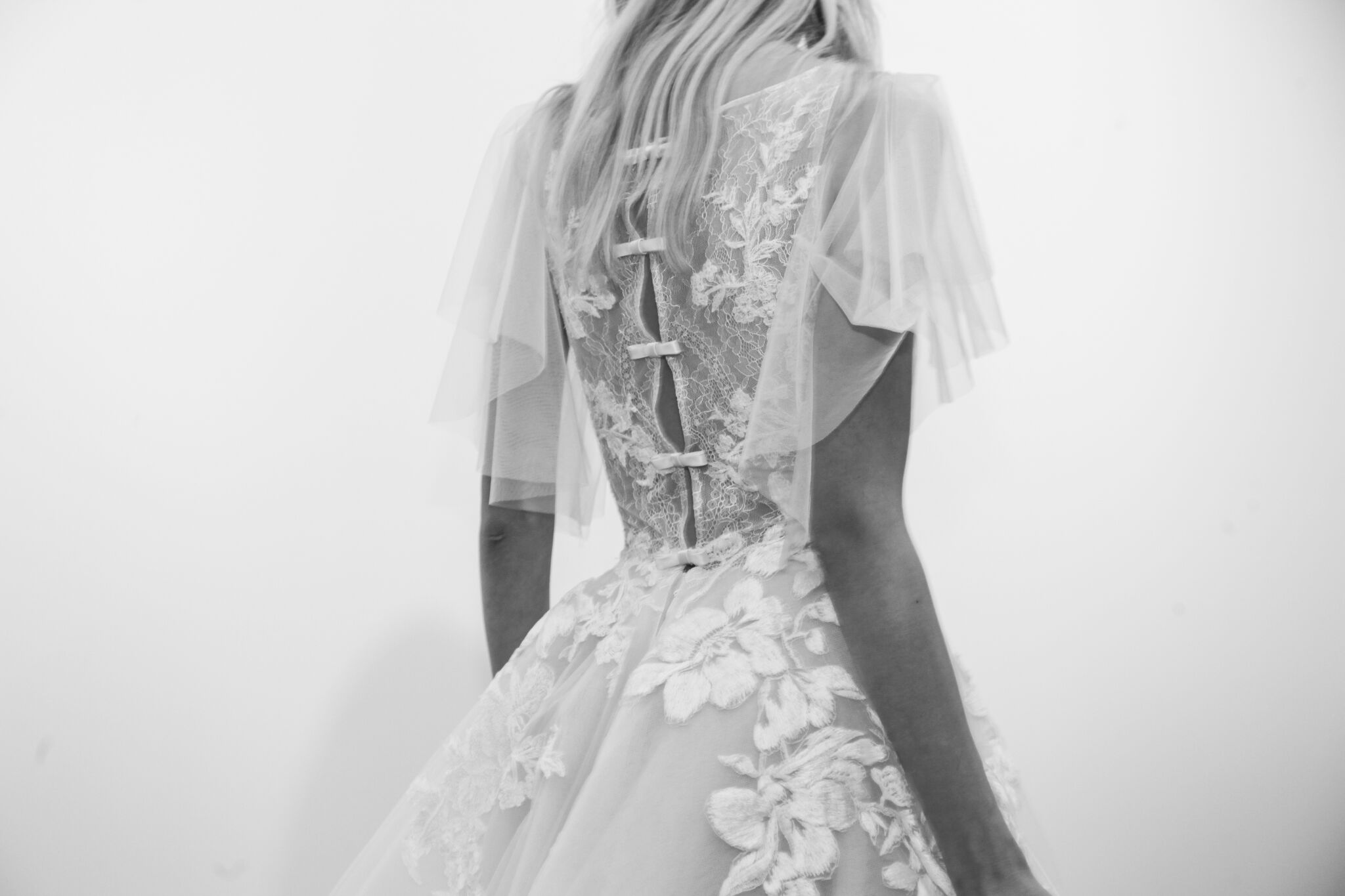 Bliss Monique Lhuilier shows a feminine wedding dress look with tailored bows and a sheer petal sleeve.