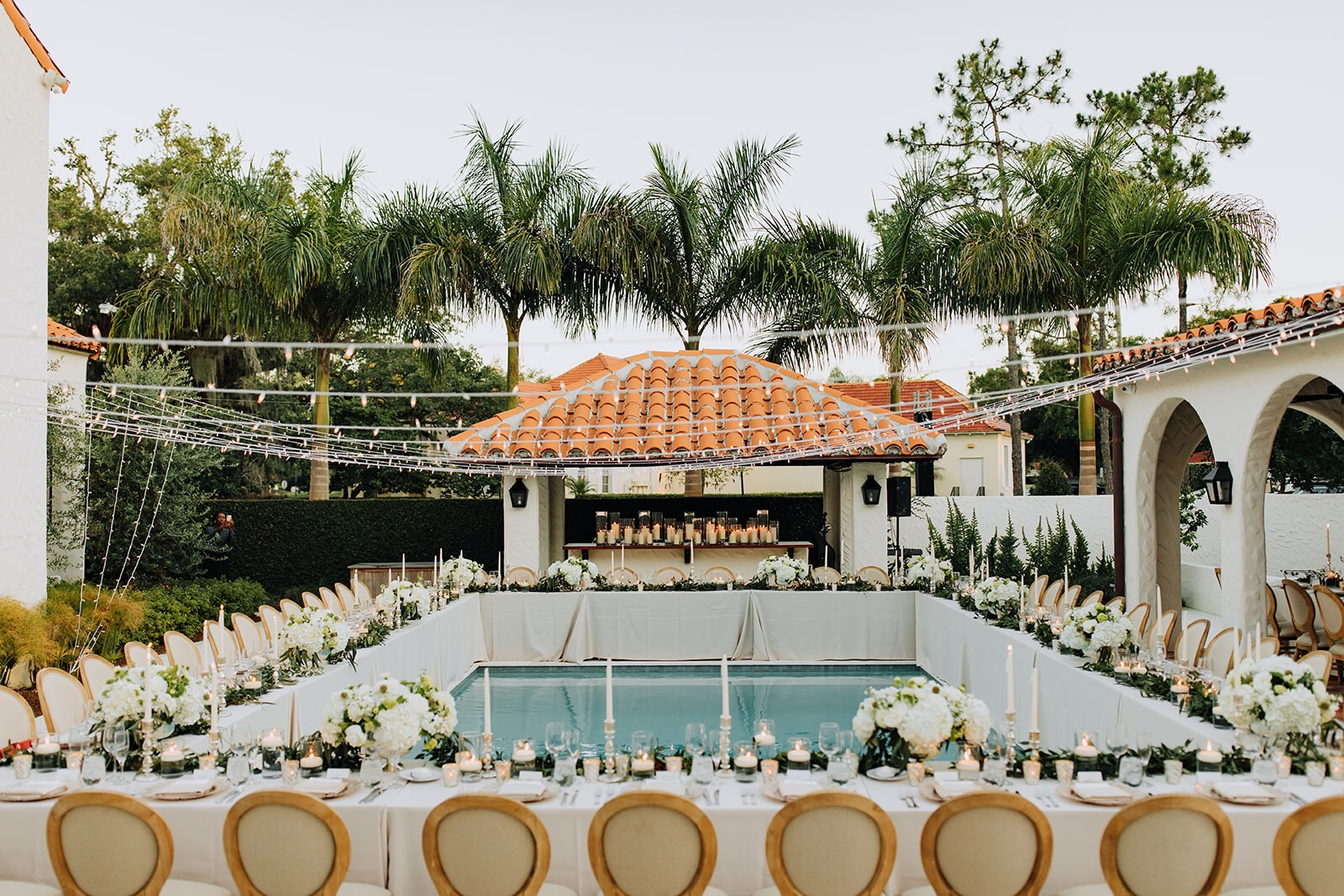 Pool side wedding reception in Winter Park with white flowers and market lights