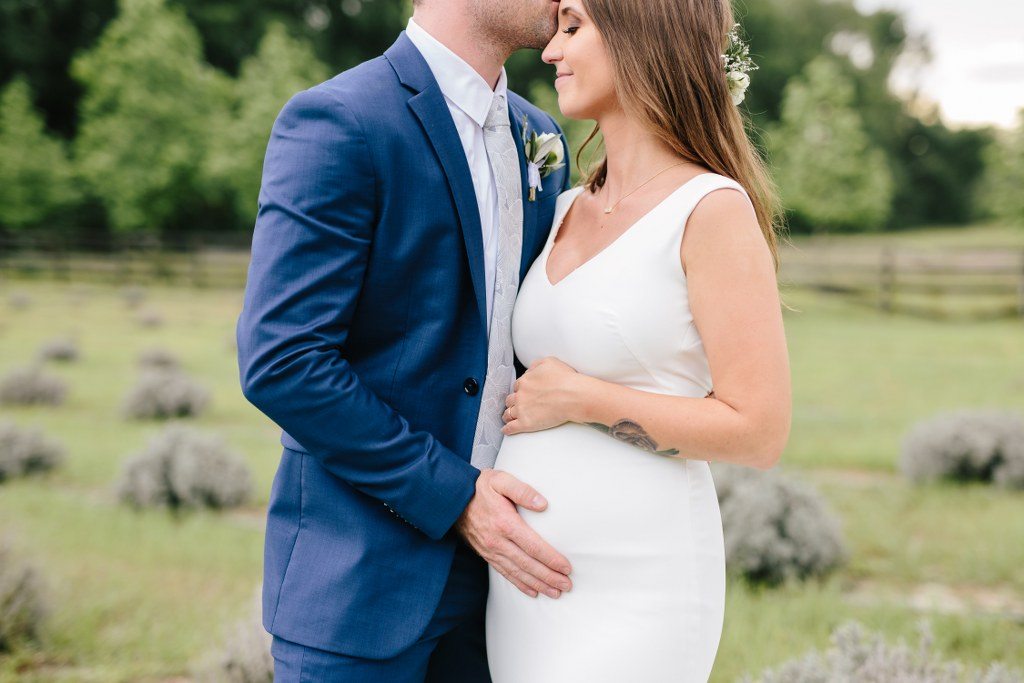 Pregnant bride on her wedding day wearing a stretch crepe wedding dress with a v neckline